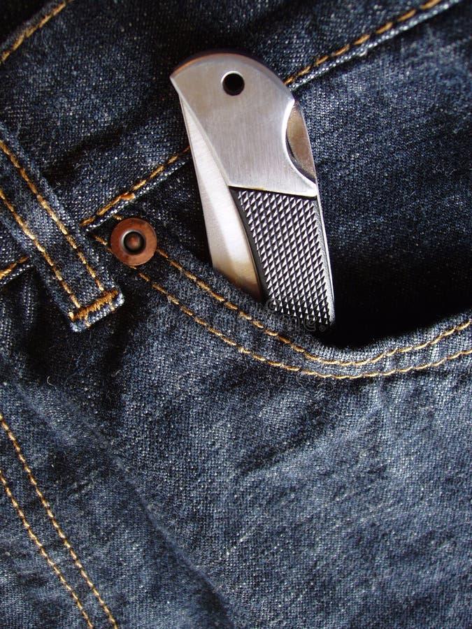 Faca de bolso no bolso das calças de brim imagens de stock royalty free