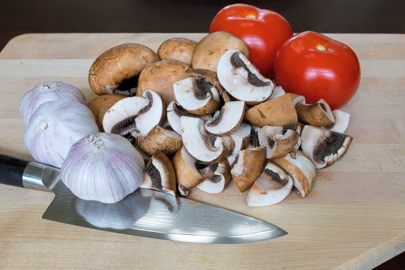 Faca de cozinha dos cravos-da-índia de alho dos tomates dos cogumelos na placa de corte fotografia de stock royalty free
