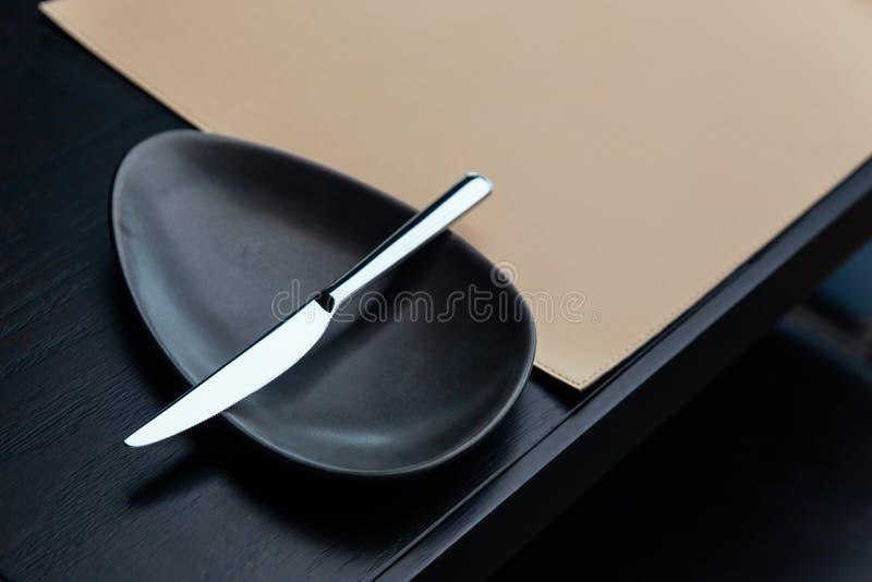 Faca de manteiga de prata na bacia preta na tabela de madeira com esteira de couro Para o jantar fino e o alimento europeu com es imagens de stock royalty free