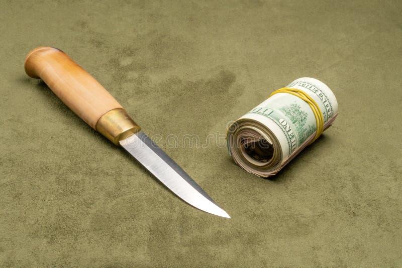 Faca e dólares torcidos no fundo verde fotos de stock royalty free