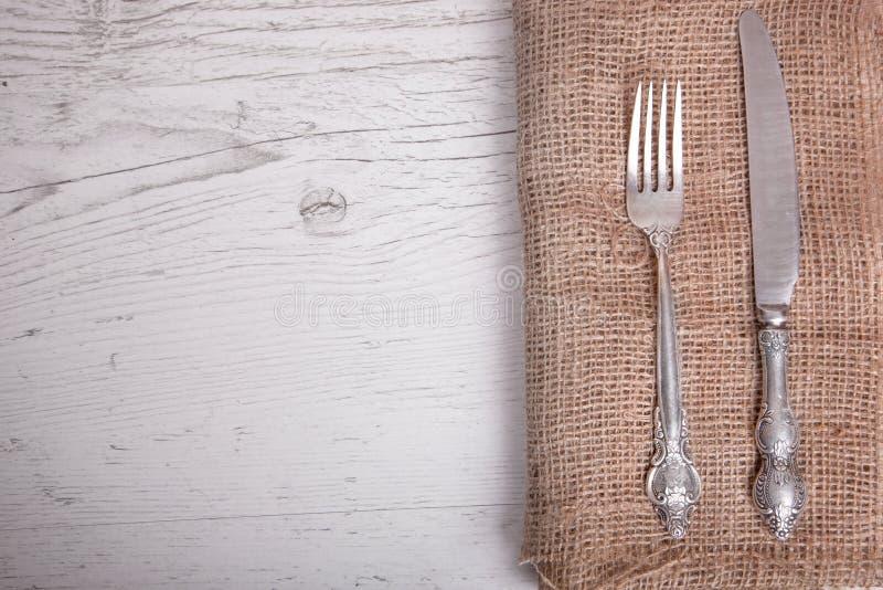 A faca e a forquilha de prata dos utensílios de mesa do vintage estão no guardanapo, em um velho imagem de stock