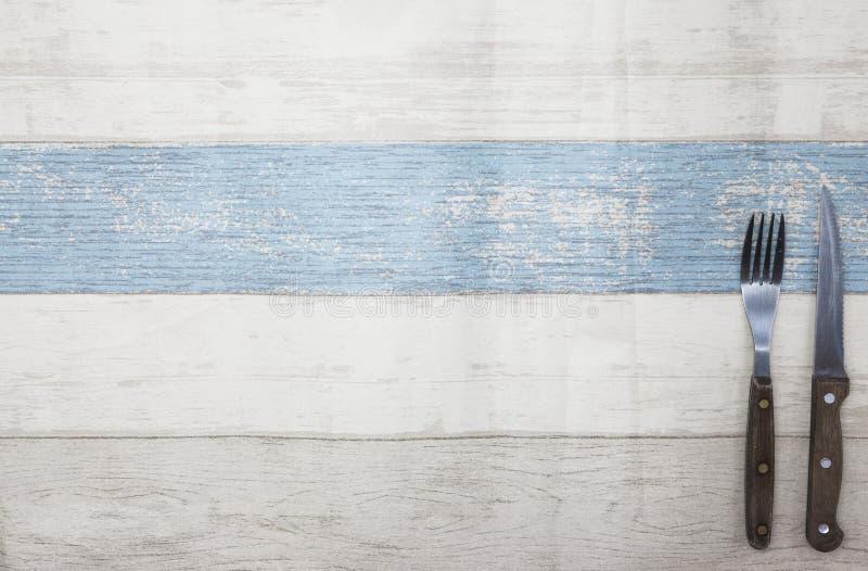 Faca, forquilha que encontra-se em um fundo de madeira claro da tabela Tabela de madeira do estilo de Provence, fundo para o menu foto de stock royalty free