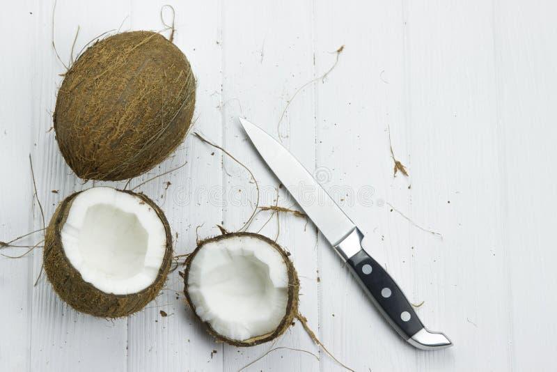 Faca orgânica branca marrom tropical fresca do leite de coco da polpa do coco no fundo branco de madeira imagens de stock royalty free