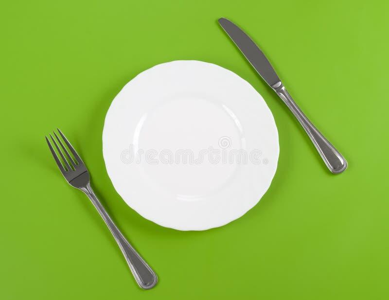 Faca, placa redonda branca e forquilha no verde fotos de stock