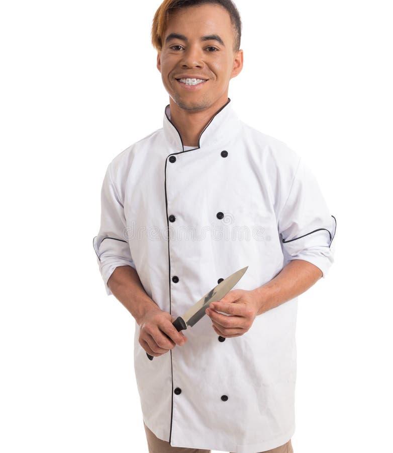 Faca profissional do cofre forte da cozinha O homem negro novo está no branco arrulha fotos de stock