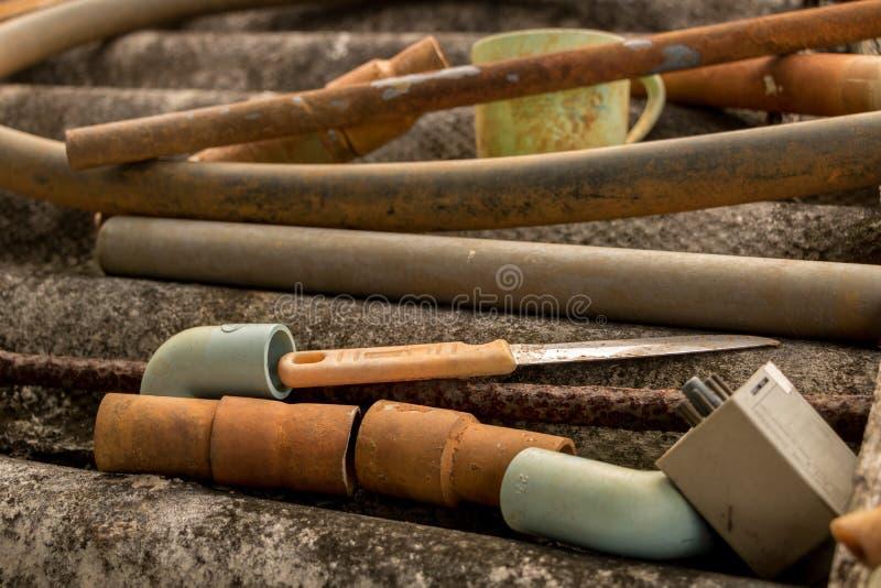 Faca velha do vintage e mangueira plástica da tubulação de água no telhado ondulado sujo - textura concreta mofado foto de stock