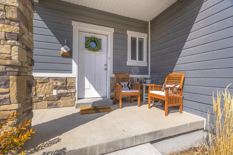 Facacde of a home with furniture on the welcoming sunlit porch. A traditional wreath is hanging on the glass paned white front door royalty free stock photography