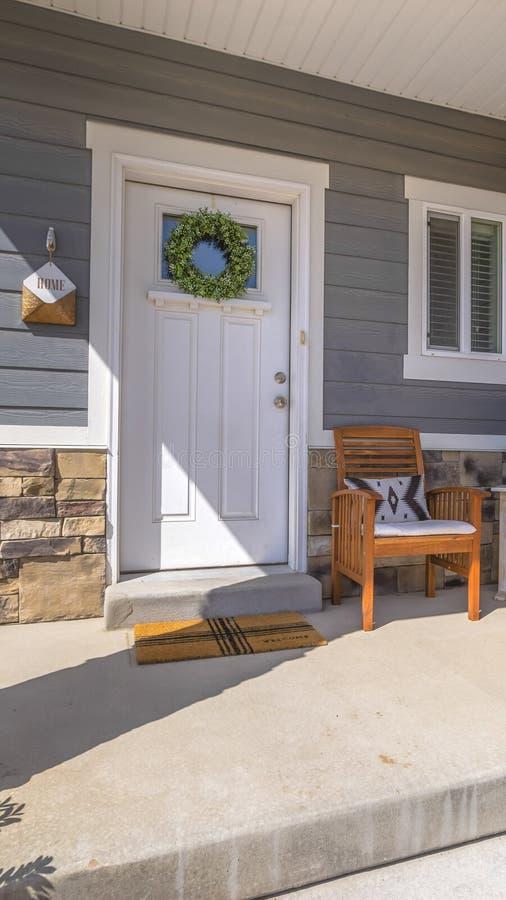 Facacde vertical de un hogar con muebles en el pórtico iluminado por el sol que da la bienvenida fotos de archivo