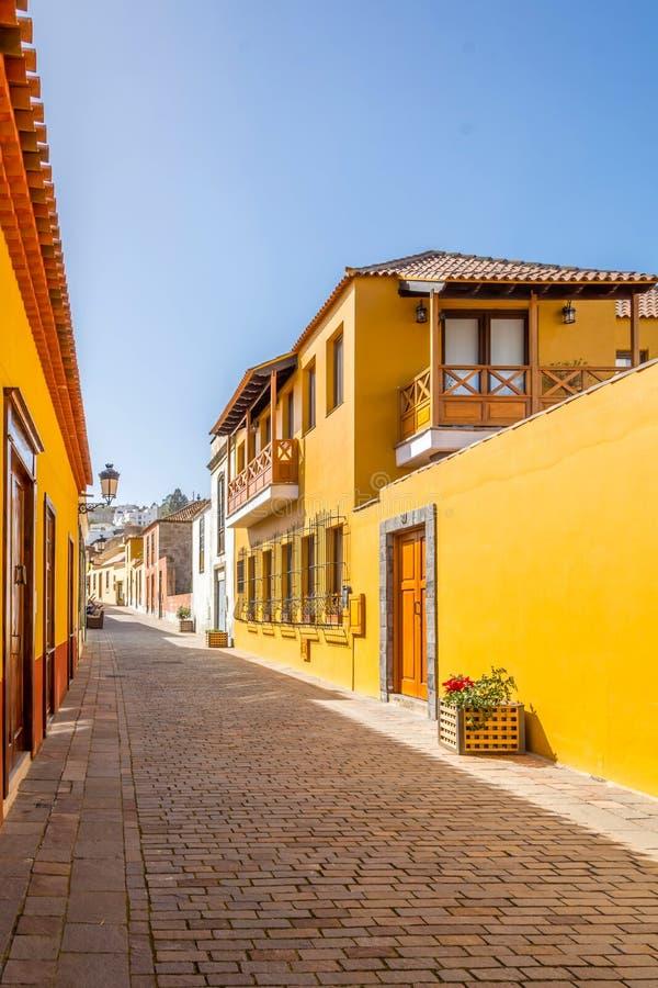 Facadas de casas antigas amarelas com janelas e portas de madeira castanhas e uma varanda fotos de stock