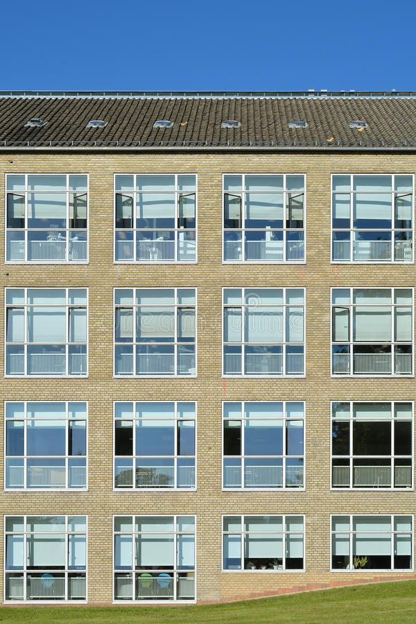 Facade, Aarhus University, Denmark. A modernistic yellow brick facade of Aarhus University with large square windows royalty free stock images