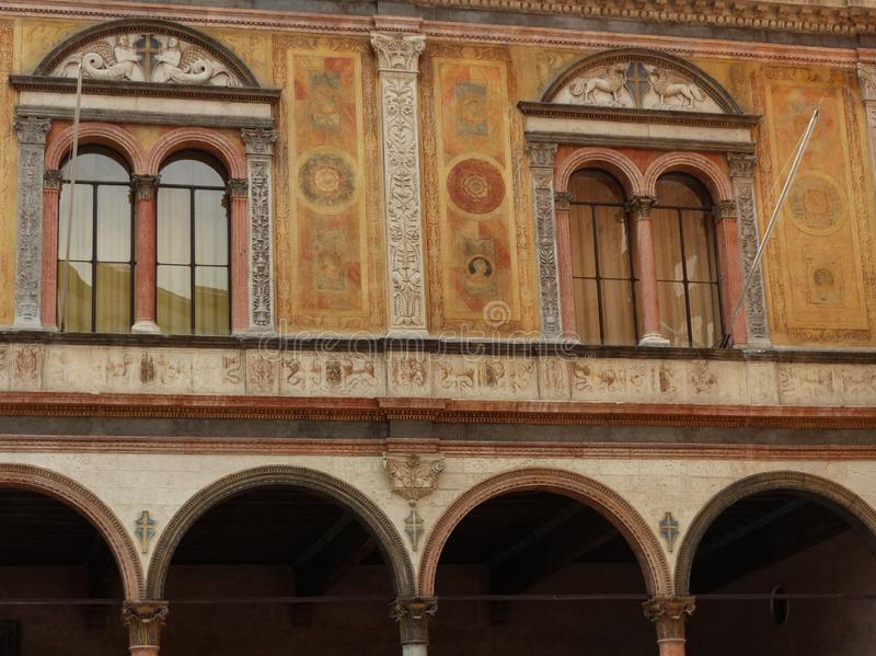 Facade of an ancient palace with decorations on the walls and arched windows to Verona in italy. royalty free stock images