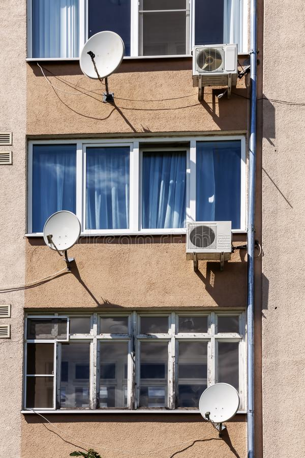 The facade of an apartment building with air conditioning and satellite television antennas. Architecture, dwelling, exterior, home, house, modern, residential stock photos