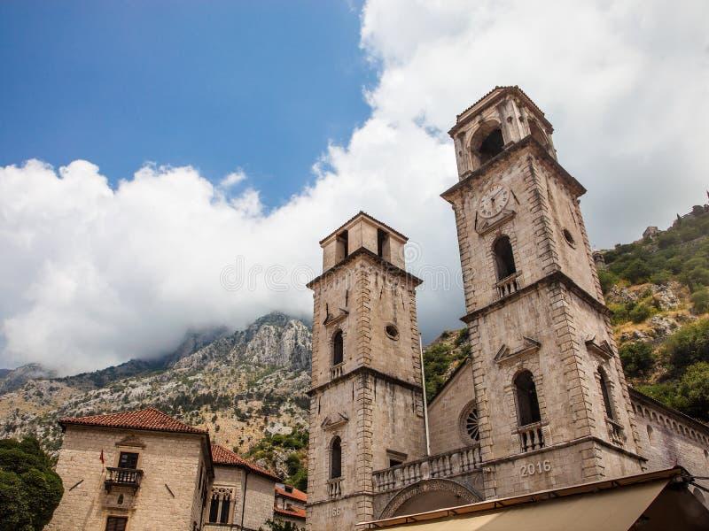 Facade av domkyrkan Sanktt Tryphon i Kotor, Montenegro Skjutit in mot berget i en ljus solig dag med fästningen på th royaltyfria bilder