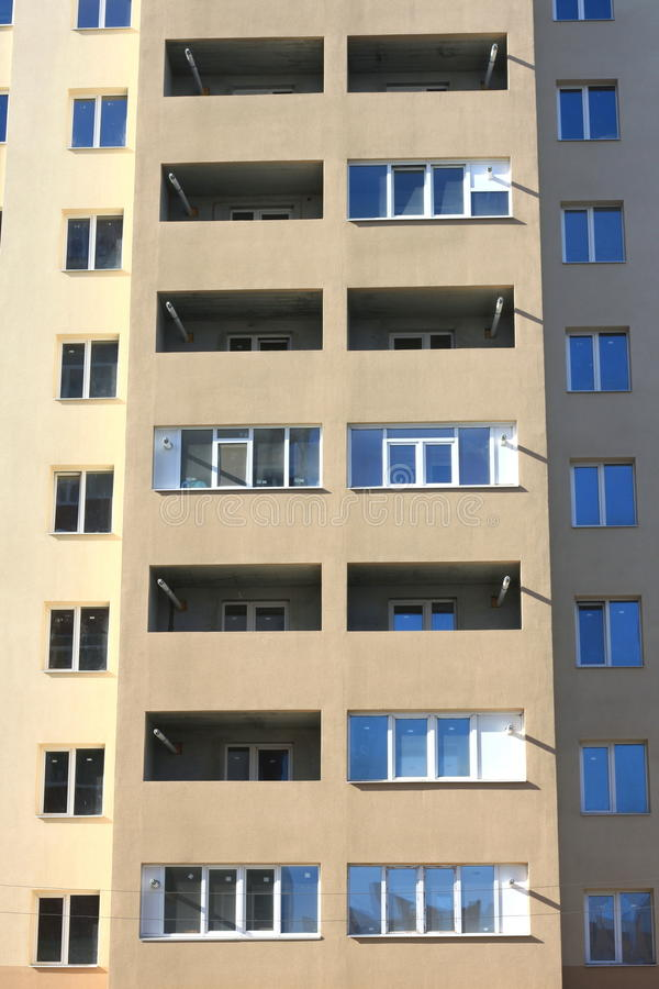 Facade of a beautiful multi-storey modern building with windows and balconies close-up stock photos