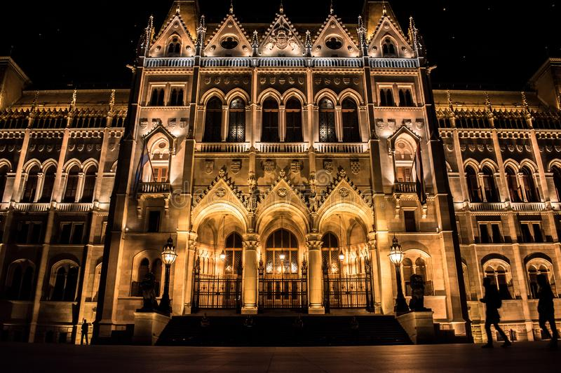 Facade of the Budapest Parliament at night with silhouettes of tourists strolling, Hungary stock photo