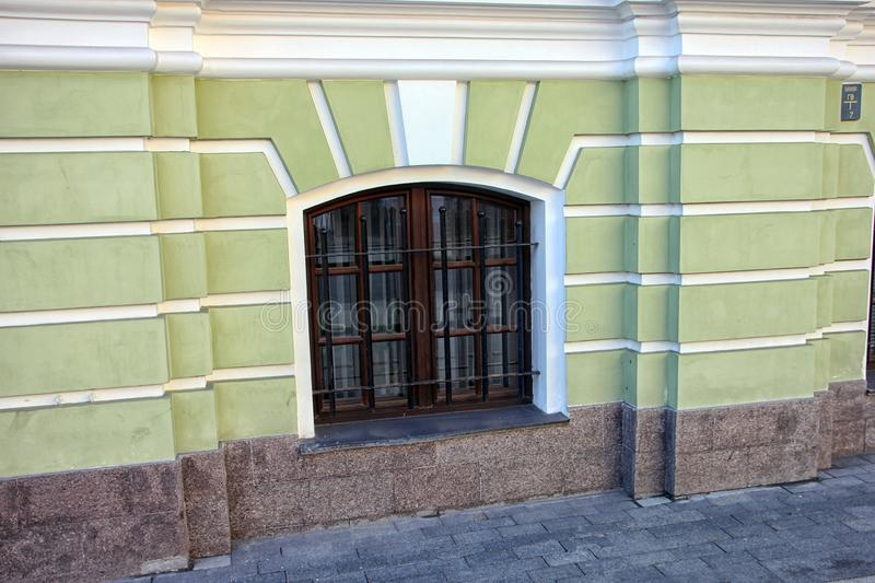 Facade of building with ground floor with green wall and bars on windows outside in Moscow street. In russia royalty free stock photography