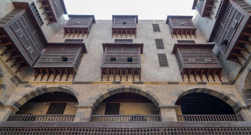 Facade of caravansary Wikala of al-Ghuri, Medieval Cairo, Egypt. Low angle view of the facade of caravansary Wikala of al-Ghuri with vaulted arcades, wooden stock photography