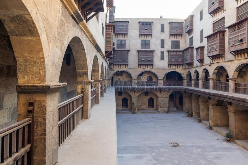 Courtyard of Caravanserai of Bazaraa, with arab oriel window, Cairo, Egypt. Facade of Caravanserai of Bazaraa, with vaulted arcades, windows, and arab oriel royalty free stock photography