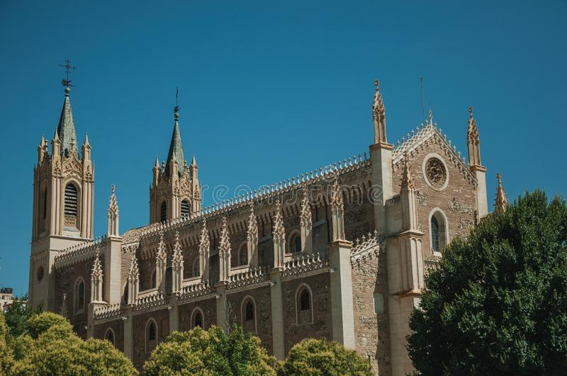 Facade of Cathedral in Gothic style among leafy trees in Madrid royalty free stock image