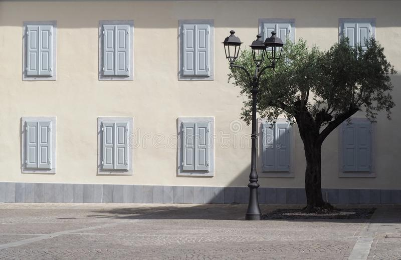 Facade of a central european town palace from the early twentieth century, with a lamppost, an olive tree. and a  porphyry street. Background for copy space stock photos
