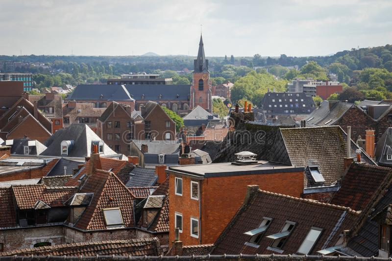 The facade of the church in the city center surrounded by houses with red tiles on the roof. Namur, Belgium - August 19, 2018: the facade of the church in the stock photography