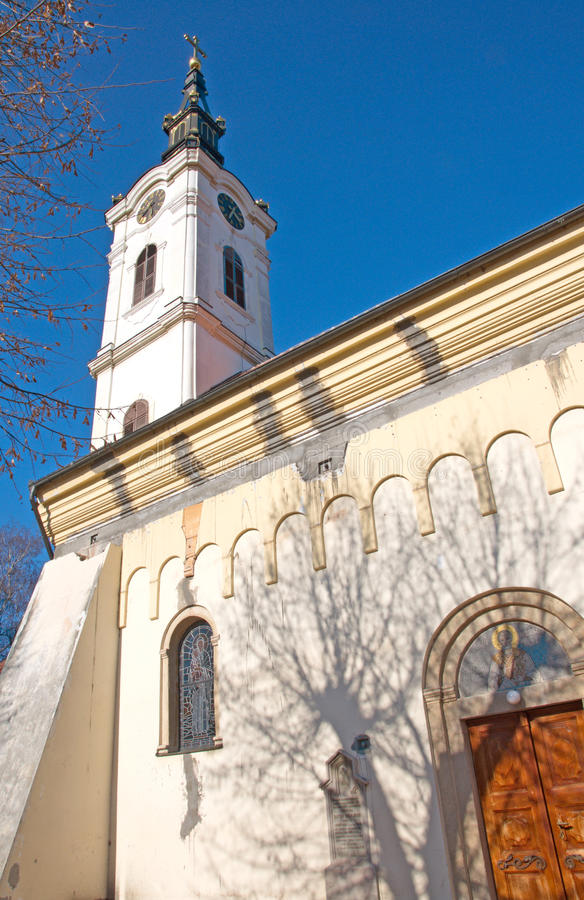 Facade and church tower with a clock at the old quarter Gardos, Zemun. Details of the facade and luxury, glided church tower with a clock at the old quarter royalty free stock photography