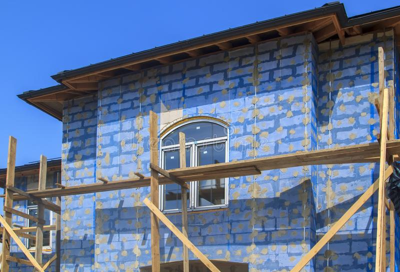 Facade of cottage under construction with building grid applied to walls and guides for plaster application. Industrial, plastic, object, block, line, concrete stock images