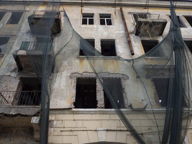 Facade de um prédio arruinado abandonado com janelas quebradas e tecido rasgado pendurado nas paredes, local do filme de terror imagem de stock