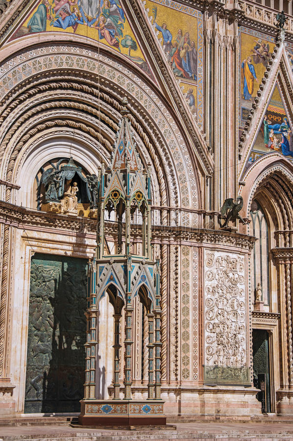 Facade details of the opulent and monumental Orvieto Cathedral in Orvieto. Facade details of the opulent and monumental Orvieto Cathedral Duomo under sunny blue stock image