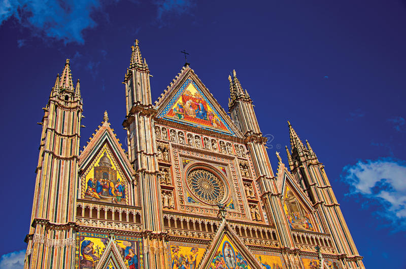 Facade details of the opulent and monumental Orvieto Cathedral in Orvieto. Facade details of the opulent and monumental Orvieto Cathedral Duomo under sunny blue royalty free stock image