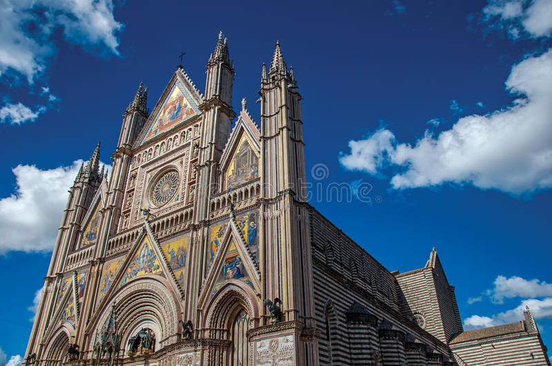 Facade details of the opulent and monumental Orvieto Cathedral in Orvieto. Facade details of the opulent and monumental Orvieto Cathedral Duomo under sunny blue stock photography