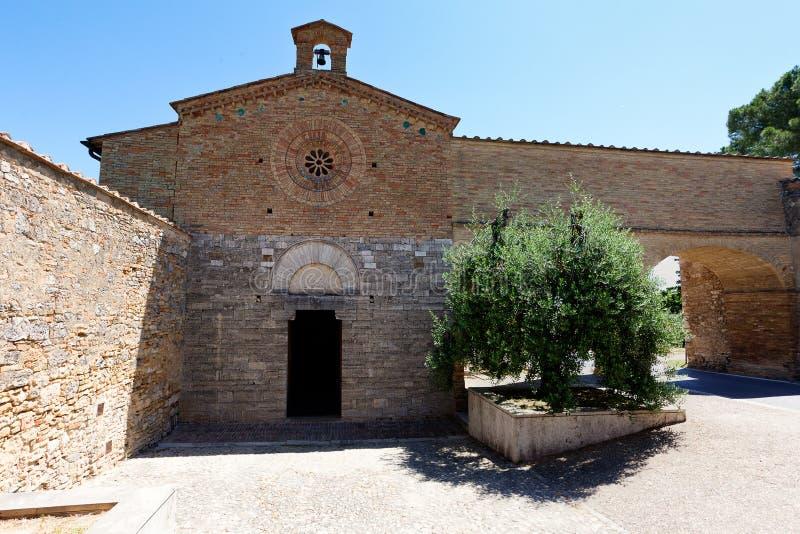 Facade chiesa di San Jacopo al Tempio Templar church Saint James, San Gimignano, Siena, Italy. The Facade with door, bell, rosetta and tree of the Roman Chiesa stock photo
