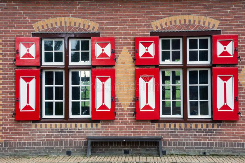 Facade of Dutch house. Two windows with red shutters. Orange brick wall. Wooden bench royalty free stock photos
