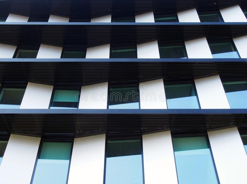 Facade of a futuristic modern building with angled geometric panels and rows of reflected windows royalty free stock photography