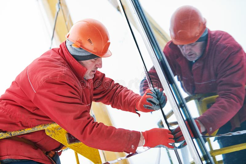 Facade glass window installation. Male industrial builder worker at facade glazing stock photography