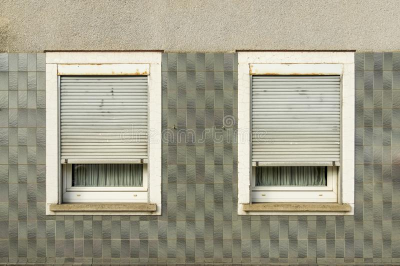 Facade half tiled, plastered over windows with half-closed shutters and windowsill probably from the 60s. In germany stock photography