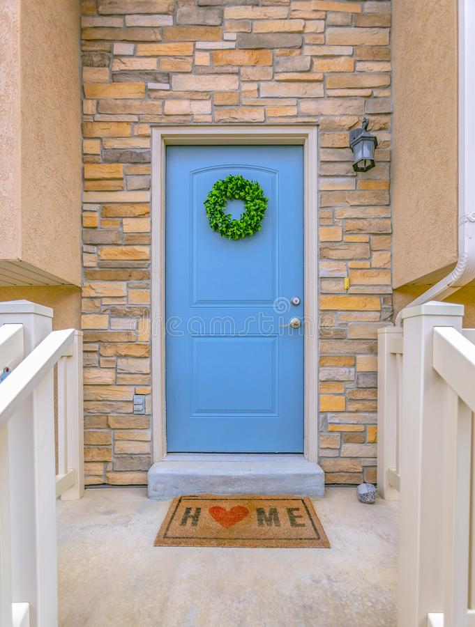 Facade of a home with blue front door and lamp on the stone brick wall stock photos