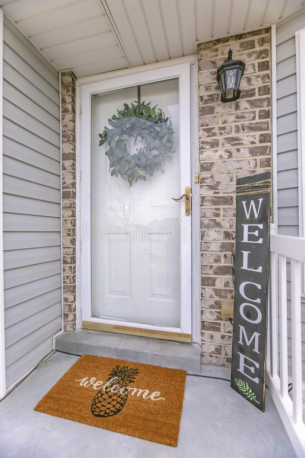 Facade of home with a leafy wreath hanging between the glass and wooden door stock image