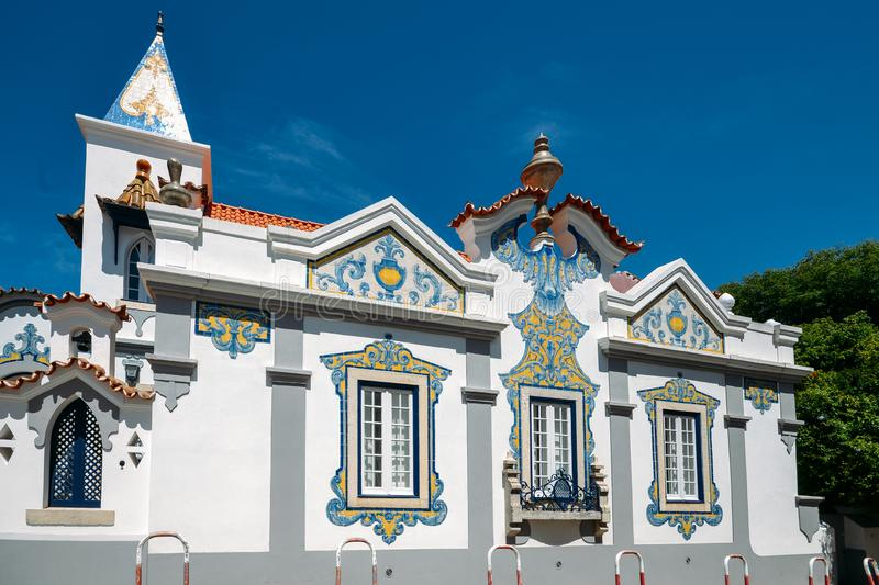 Facade of house covered in blue Portuguese style azulejo tiles in Cascais, Portugal. Cascais, Portugal - May 3rd, 2019: Facade of house covered in blue royalty free stock image