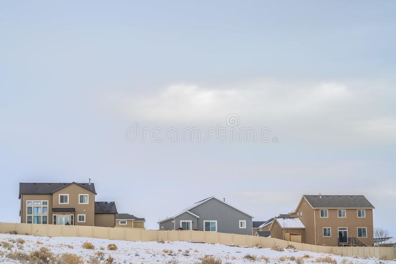 Facade of houses with a boundless cloudy sky background in winter. A terrain coated with fresh powdery snow cna be seen in front of the wooden fence stock photo