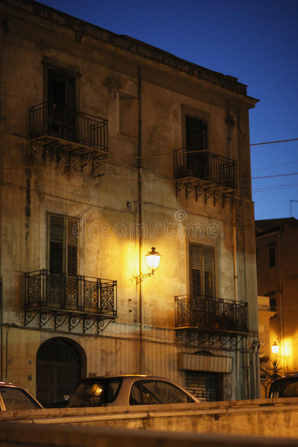 Facade of houses. Facade of old racy houses with balconies and a lantern in the night sky in Palermo, Italy royalty free stock photo