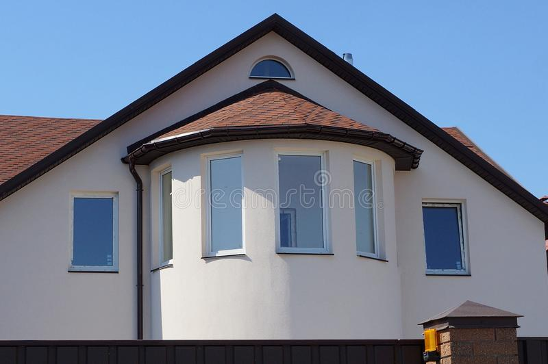 Facade of a large house with a loft and windows and brown tiles on the roof against the sky stock photos