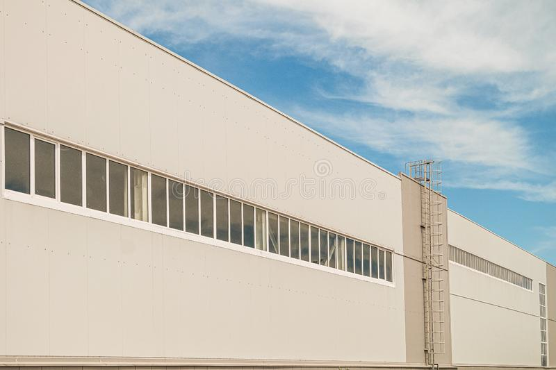 Facade of a long multi-span industrial building under a blue cloudy sky royalty free stock image