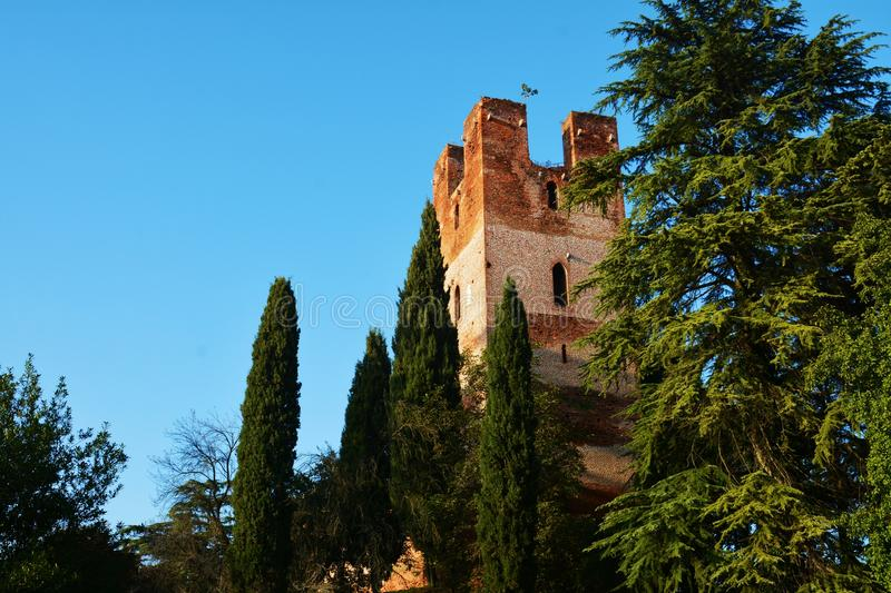 Facade of medieval tower and trees, Castelfranco Veneto. Medieval walls, trees and tower against the blue sky in Castelfranco Veneto, Italy, Europe royalty free stock photos