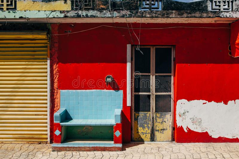 Facade of a mexican house on the island of Cozumel. Red shabby wall and blue bench stock image