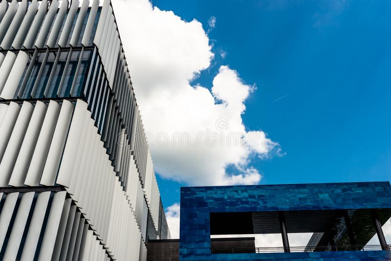 The facade of a modern building with an innovative facade made of automatic, movable blinds against the background of blue sky wit stock photography