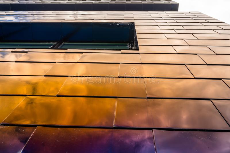 The facade of a modern building made of glass, blue panels in which the sky is reflected. royalty free stock images