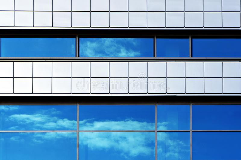 Facade of modern building. Reflection of sky and clouds in windows. royalty free stock image