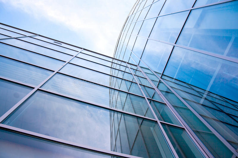 Facade of modern glass blue office and clouds stock photo
