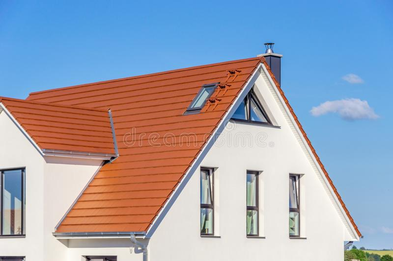Facade of a modern house with red tiled roof, blue sky royalty free stock photography
